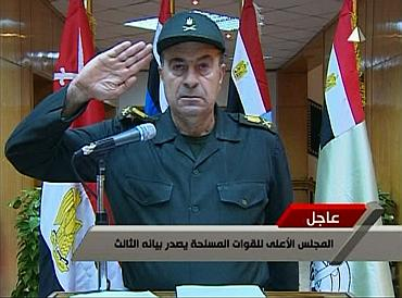 A spokesman for Egypt's higher military council salutes while reading a statement on transition of power