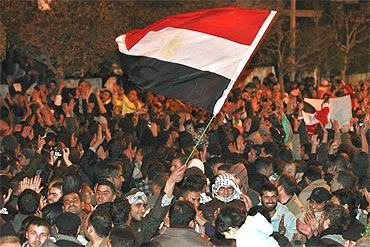 Protesters wave an Egyptian national flag as they celebrate after the announcement of President Hosni Mubarak's resignation on Friday