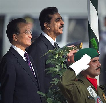 Pakistan Prime Minister Yousuf Raza Gilani and Chinese Premier Wen Jiabao listen to the national anthems of both countries during an official ceremony in Islamabad