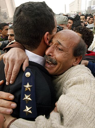 An Egyptian policeman is hugged by an opposition supporter in Tahrir Square