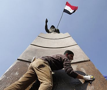A man cleans the base of the statue of Egyptian Army General Abdul Moneim Riyad at Tahrir Square