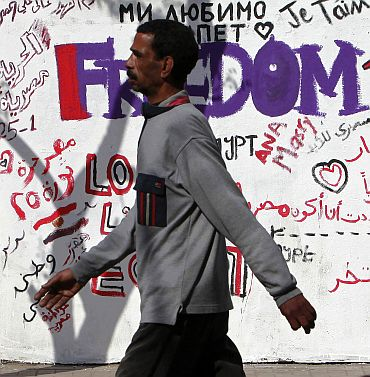 People walk past slogans near Tahrir Square