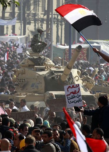 An Egyptian soldier atop a tank watches opposition supporters during a huge rally