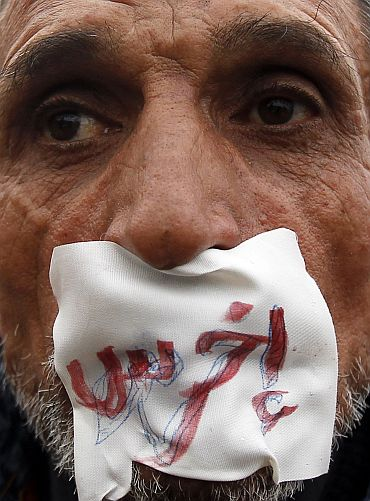 An anti-government demonstrator looks on with a sign reading 'shut up' over his mouth