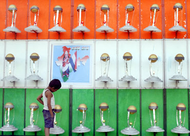 A child looks at models of the ICC Cricket World Cup trophy in Hyderabad. Artist T Vishnu built 51 models of the World Cup trophy, wishing the Indian team good luck.