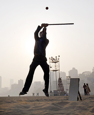A man hits a ball by the beach with a stick for a bat and a piece of wood for wickets in Mumbai.