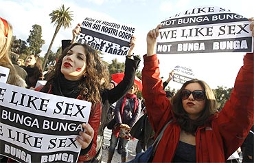 Women hold placards during a demonstration against Berlusconi