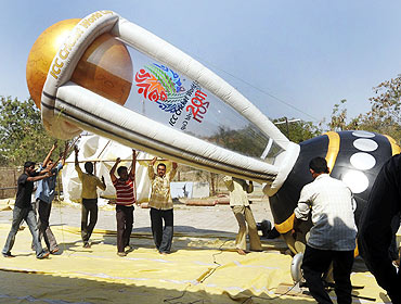 Workers erect an inflatable model of the 2011 Cricket World Cup trophy in Hyderabad