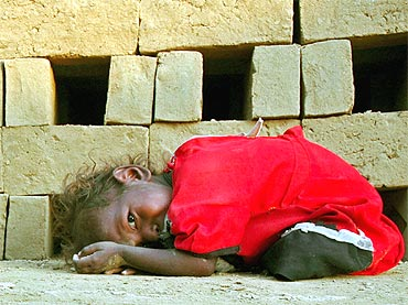 A child of a brick kiln worker rests at a brick factory in Gadopur village near Allahabad