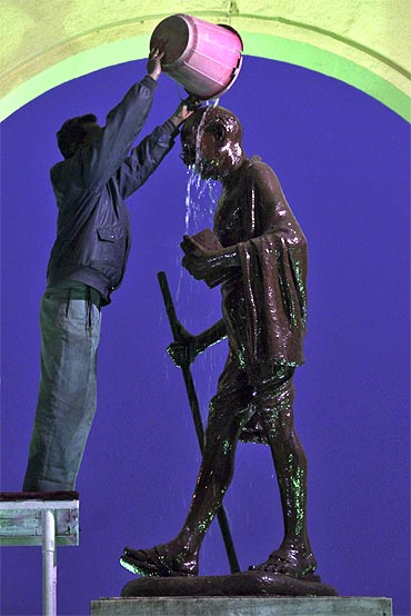 A worker cleans a statue of Mahatma Gandhi in Lucknow