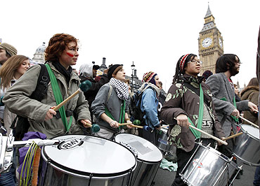 Demonstrators play drums during a march protesting the raising of student tuition fees in London