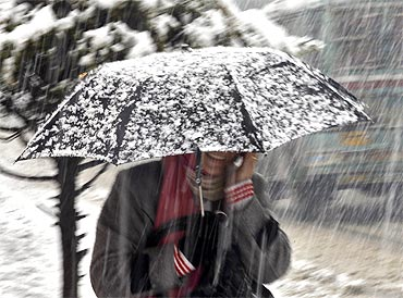 A Kashmiri woman carries an umbrella during snowfall in Srinagar