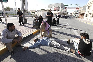 A protester collapses after inhaling tear gas during a demonstration in Manama