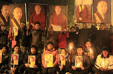 Tibetan exiles hold portraits of Karmapa Lama during a candlelight vigil in New Delhi