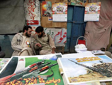 Supporters of Jamate-e-Islami sit next to posters and materials about Jihad in Peshawar