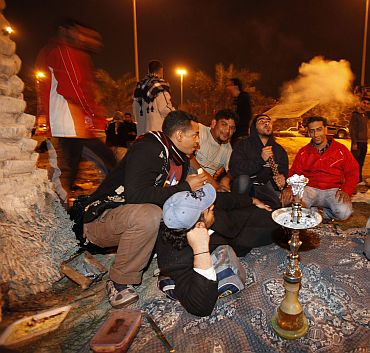 Hours before the riot police stepped in, protesters are seen sitting near a traditional Arabic shisha pipe as they camp out at the Pearl Roundabout