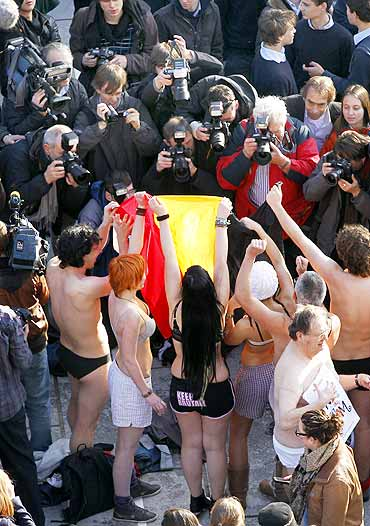 Belgians take part in a mass striptease.