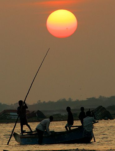 Fishermen row a boat at sunset in Nagaipattinam, Tamil Nadu