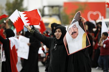 A Bahraini woman holds a picture of Prime Minister Prince Khalifa bin Isa al-Khalifa as she shouts pro-government slogans during a pro-government rally in Riffa