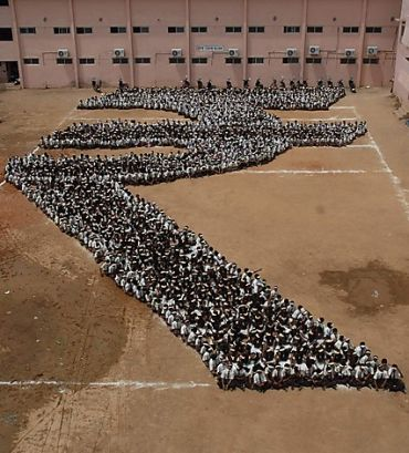 Students make a formation of the new symbol of the Indian rupee at a school in Chennai