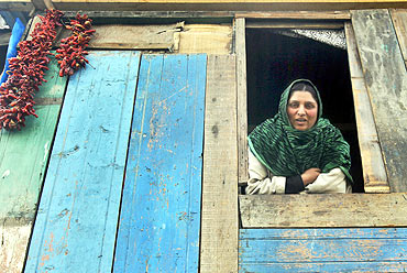 A Kashmiri woman at the window of her makeshift home on the banks of Jhelum river in Srinagar