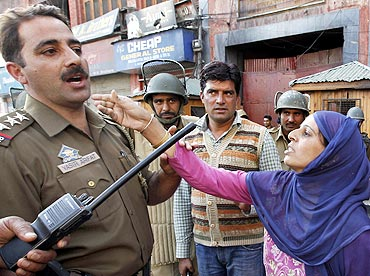 A Kashmiri woman pleads with a police officer to release her relative detained during an anti-India protest in Srinagar