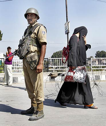 A Kashmiri woman walks past a policeman standing guard at a barricade during a curfew in Srinagar