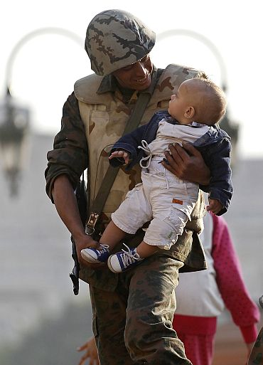 An Egyptian soldier holds a baby on top of his tank as he poses for photographs inside Tahrir Square