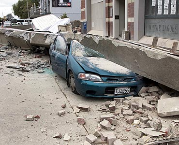 A car is crushed by fallen concrete after an earthquake in central Christchurch