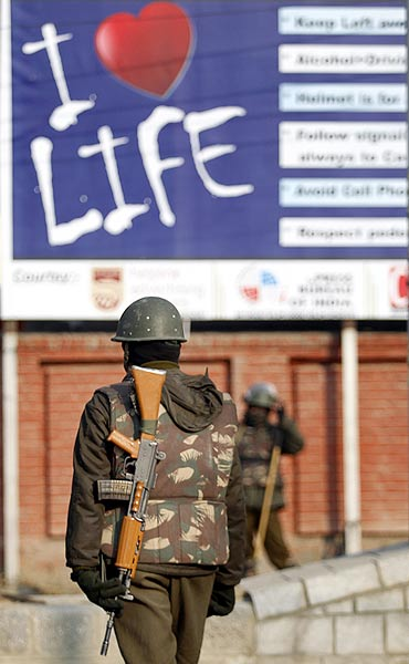 Policemen stand guard at a barricade at Lal Chowk, Srinagar