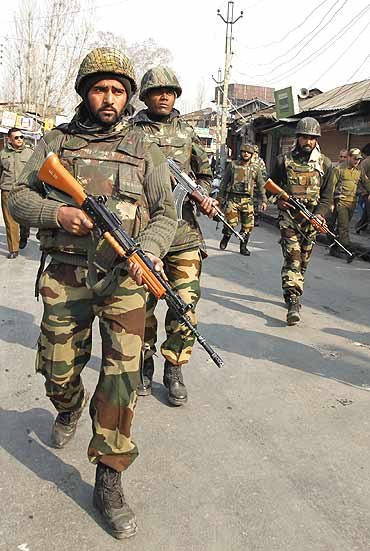 Army soldiers patrol the scene of a shootout in Srinagar