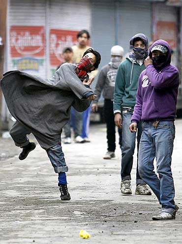 A Kashmiri protester throws stones at policemen