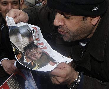 A demonstrator spits at a picture of Libya's Muammar Gaddafi