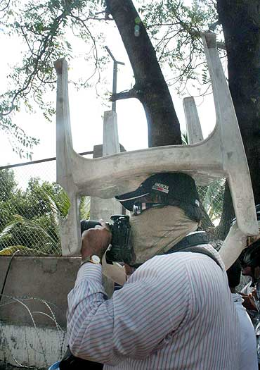 A photojournalist covers his head with a chair to protect himself while covering the protests in Hyderabad on Tuesday