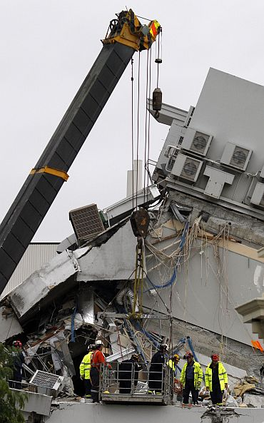 Emergency workers are lifted into the remains of the Pyne Gould Guinness building