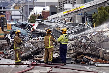 Firemen hose down the rubble of the CTV building which was devastated by a 6.3 magnitude earthquake in central Christchurch