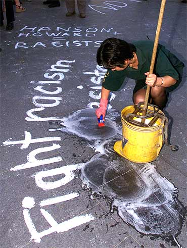 An ethnic Chinese cleaner scrubs off anti-racist slogans scribbled on the street by protesting students in Sydney