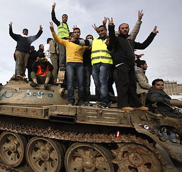 Anti-government protesters make victory signs as they stand on an army tank