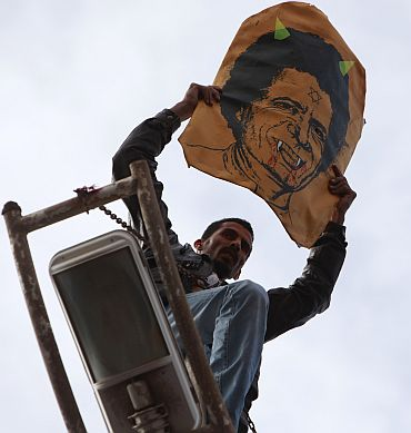 A protester holds a poster depicting Libyan leader Muammar Gaddafi as he stands over a lamp post in Benghazi city