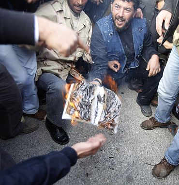 Protesters burn a copy of the Green Book written by Libyan leader Muammar Gaddafi as they chant anti-government slogans in the main square in Tobruk