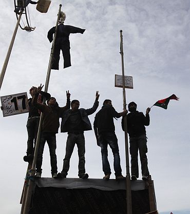 Protesters chant anti-government slogans while an effigy depicting Libyan leader Muammar Gaddafi is hung in a square in Benghazi city