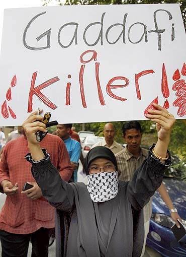 A protester holds a placard during a demonstration against Libya's leader Muammar Gaddafi