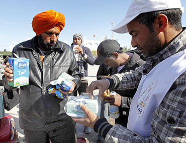 Indians fleeing unrest in Libya receive food and drinks after crossing the border into Tunisia