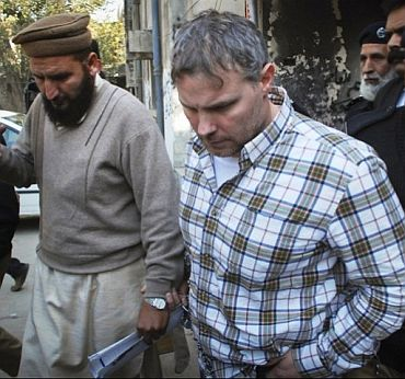 Alleged CIA operative Raymond Davis being escorted by police and officials out of court after facing a judge in Lahore