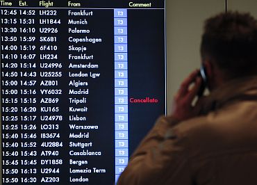 A man talks on the mobile phone as he watches the flight board showing a cancelled flight from Tripoli at the Leonardo Da Vinci International airport in Rome