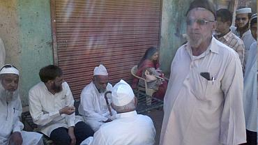 Syed Umerjee sits with his neighbours at his home near Godhra