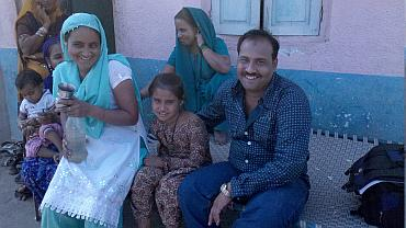 Sadiq with his wife and daughter outside their home