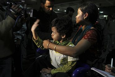 A boy gestures to a newsman upon his arrival at the airport in New Delhi from Libya