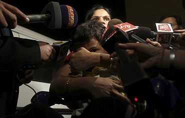 A family is mobbed by reporters after their arrival from Libya