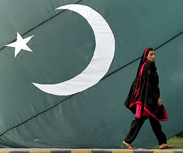 A woman walks past a Pakistani flag